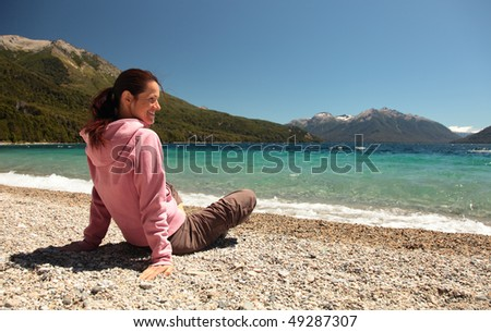 A woman sits at the edge of a clear blue lake in southern Argentina.