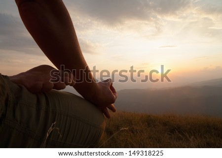 A woman sits in lotus position facing a sunset./Woman meditating towards a sunset close-up - stock photo