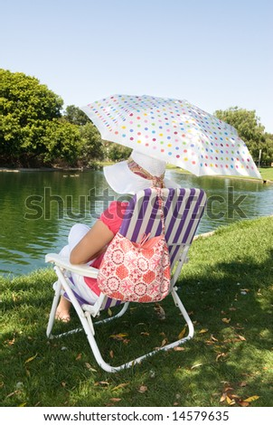 A woman sits near the edge of a lake while relaxing on a Sunday morning. - stock photo