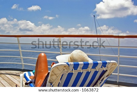 A woman sits on the upper deck of a cruise ship and overlooks the ocean - stock photo