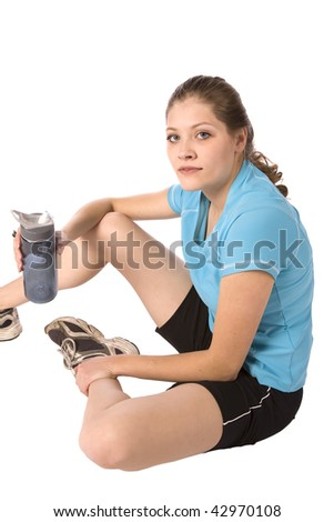 A woman sitting after exercising with a water bottle in her hand, and a serious look on her face. - stock photo