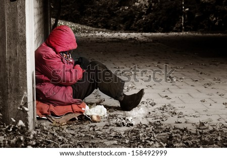 A woman sitting against a brick building with her head in her arms - stock photo