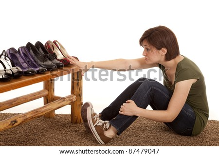 A woman sitting and looking at all the new shoes she wants some but can not have them.