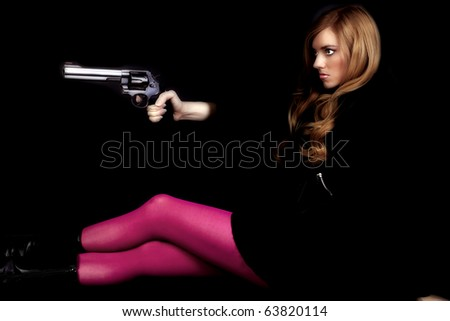 a woman sitting and looking away while holding a gun with pink tights. - stock photo