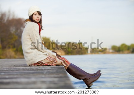 A Woman Sitting And Smiling On The Riverside - stock photo