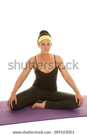 a woman sitting and stretching out her legs, in a yoga pose. - stock photo