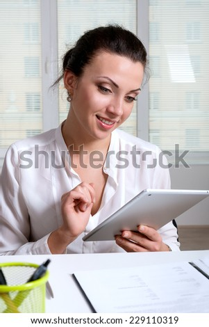 A woman sitting at a desk in an office is studying the information on the tablet