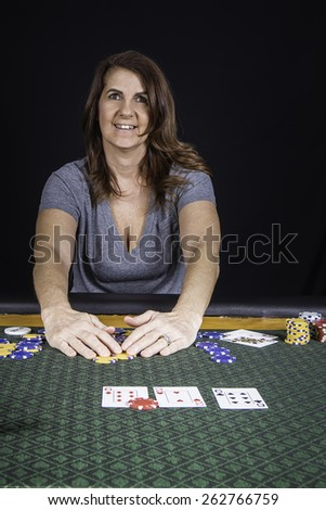 A woman sitting at a poker table playing cards with a black background - stock photo