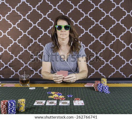 A woman sitting at a poker table wearing sunglasses playing cards with a brown background - stock photo