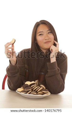 A woman sitting at a table looking at one cookie - stock photo