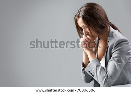 A woman sitting at table and praying - stock photo