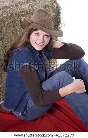 A woman sitting by a hay bale while holding her hat wearing denim with a smile on her face. - stock photo