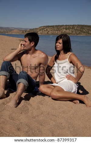 A woman sitting by her man while he is on the phone ignoring her. - stock photo
