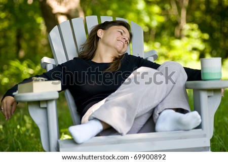 A woman sitting comfortably in an outdoor adirondack chair, with a coffee mug on one arm, and a book on the other.
