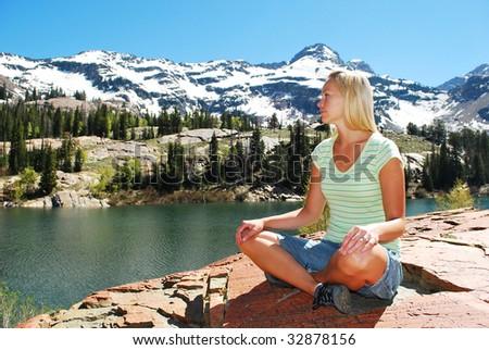 A woman sitting cross-legged next to a mountain lake. - stock photo