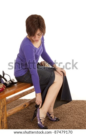 A woman sitting down and putting on a new pair of shoes. - stock photo