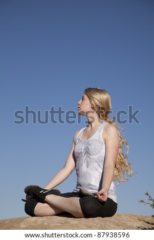 A woman sitting down on a rock doing a yoga relaxing pose. - stock photo