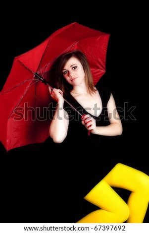 A woman sitting holding a red umbrella and wearing yellow tights with a serious expression on her face.