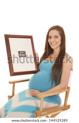 a woman sitting in a chair holding up a ultrasound picture of her baby with a smile on her face - stock photo