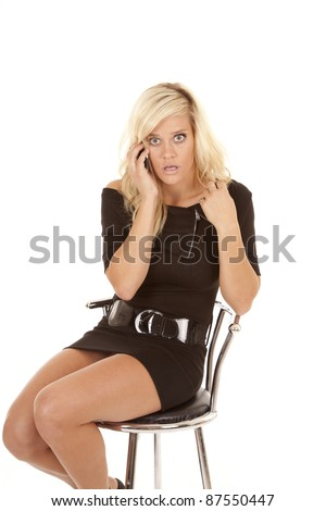 A woman sitting in a chair talking on the phone with a shocked expression on her face.