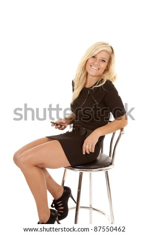 A woman sitting in a chair with a smile on her face holding on to her phone.