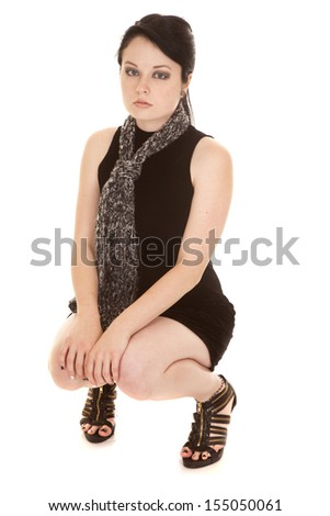 A woman sitting in a squat position in her black dress with a serious expression on her face - stock photo