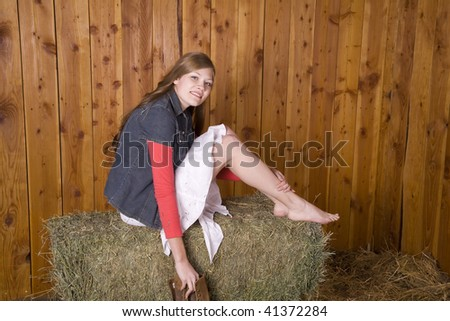 A woman sitting in a white skirt on top of a hay bale with bare feet holding her boots and smiling. - stock photo