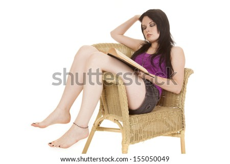 a woman sitting in a wicker chair looking at her book reading. - stock photo