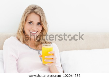 A woman sitting in bed with a glass of orange juice while she is looking forward and smiling. - stock photo