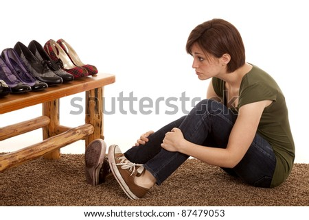 a woman sitting in front of a bunch of fancy shoes wanting them instead of what she has.