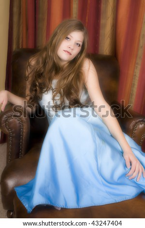 A woman sitting in her beautiful blue formal gown with a serious look on her face. - stock photo