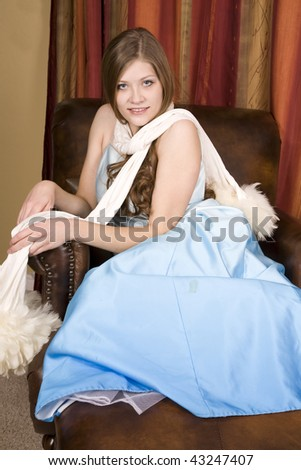 A woman sitting in her beautiful blue formal gown with a small smile on her face with her white scarf around her shoulders. - stock photo