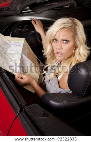A woman sitting in her car and looking at a road map with a confused expression on her face. - stock photo
