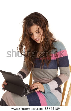A woman sitting in her chair with her small computer on her lap.
