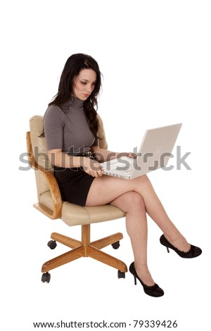 A woman sitting in her chair working on her laptop with a happy expression on her face. - stock photo