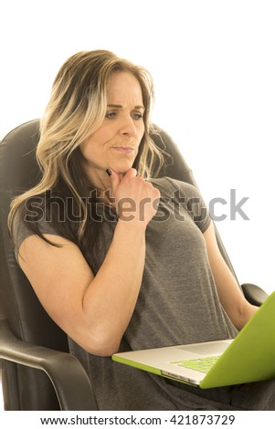 A woman sitting in her office chair, thinking about something on her laptop.