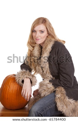 A woman sitting in her warm fuzzy coat while she leans on a pumpkin. - stock photo
