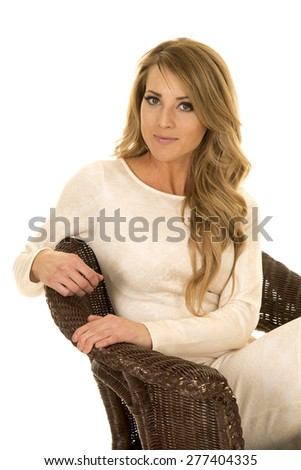 A woman sitting in her wicker chair in her white fitted dress.