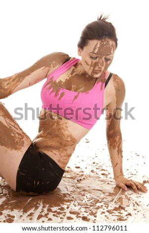 A woman sitting in mud looking down. - stock photo