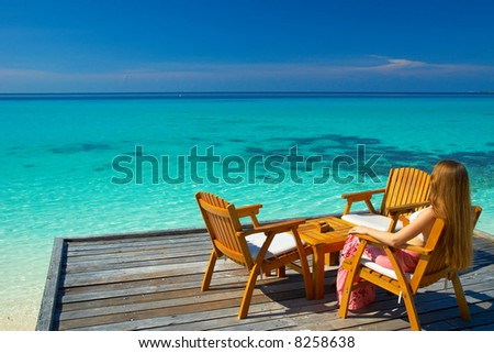 A woman sitting in the chair looking at the dreamy view on the horizon - stock photo
