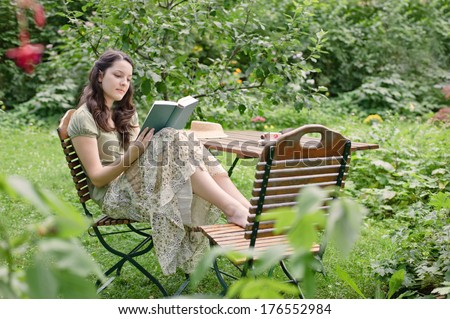 Woman Sitting Garden Reading Book Stock Photo & Image (Royalty-Free