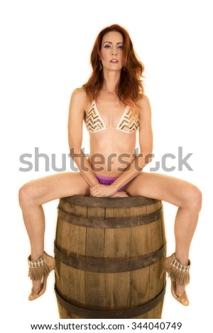 A woman sitting on a barrel with her legs apart with a sensual expression. - stock photo