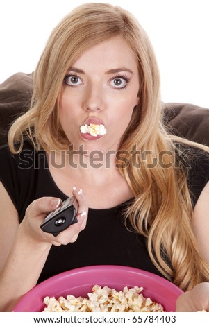 a woman sitting on a bean bag while she is enjoying her popcorn with it falling out of her mouth. - stock photo