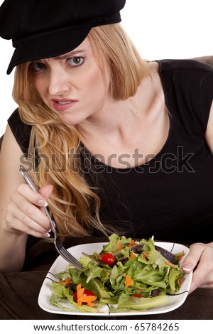 a woman sitting on a bean bag while she is showing a yucky face.  She doesn't like her salad. - stock photo