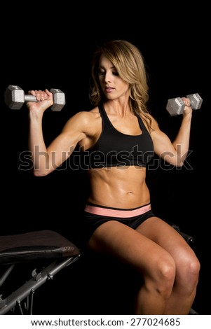 a woman sitting on a bench, doing shoulder presses.  Working her muscles. - stock photo