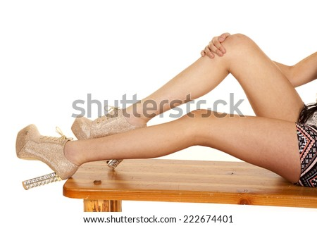 a woman sitting on a bench holding knee with heeled shoes - stock photo