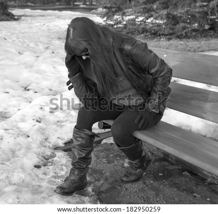 A woman sitting on a bench hunched over in disappointment