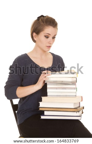a woman sitting on a chair with a shocked expression on her face, holding on to a stack of books.