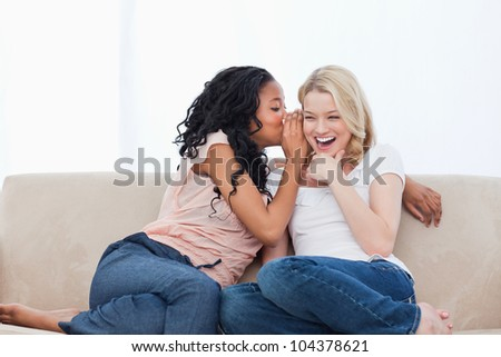A woman sitting on a couch is whispering into her smiling friends ear