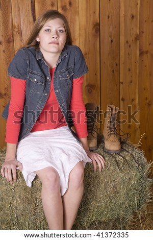 A woman sitting on a hay bale in white skirt with bare feet with small smile on her lips. - stock photo